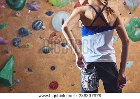 Woman Climber Preparing To Climb Indoors In Bouldering Gym With Dramatic Light. Woman Using Chalk. A