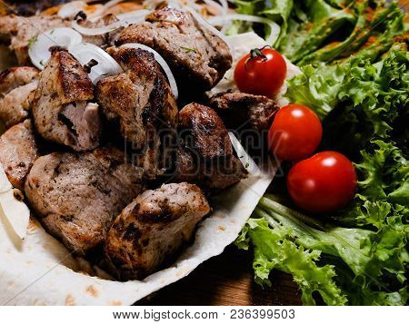 National Armenian Food. Charred Shashlik With Vegetables Background. Nutritional And Substantial Mea