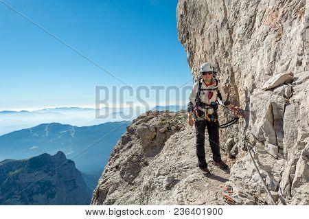 Happy Female Mountaineer Climbing Via Ferrata. Brenta Dolomites, Sentiero Delle Bocchette Alte.