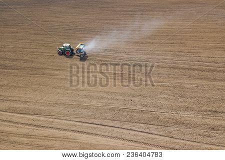 Tractor Fertilizing Field, Aerial View. Tractor Spreading Artificial Fertilizers.