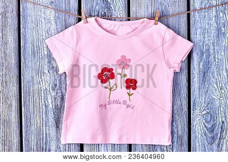 Baby-girl T-shirt Hanging On Rope. Toddler Girl Pink Cartoon Top Hanging On Clothesline On Grey Wood