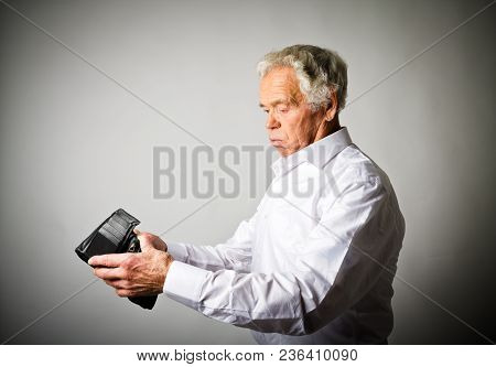Worried Old Man In White Is Looking At An Empty Wallet.