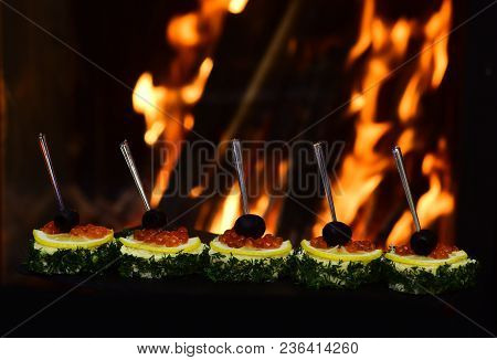 Cold Appetizers, Canape With Red Caviar, Fire On Background. Canape With Olives, Red Caviar, Lemon A