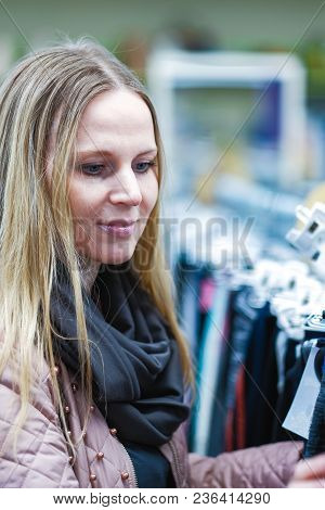 A Beautiful Middle-aged Woman Chooses To Shop In The Store