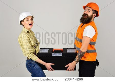 Repairman And Girlfriend Holding Toolbox Together, Copy Space. Smiling Woman In Helmet Excited About