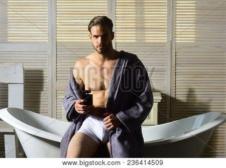 Macho With Muscular Torso In Underwear And Bathrobe On Bath. Macho With Perfume Bottle In Bathroom.
