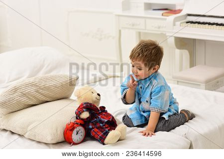 Child In Bedroom With Silence Gesture. Time To Sleep Concept. Boy With Happy Face Puts Favourite Toy