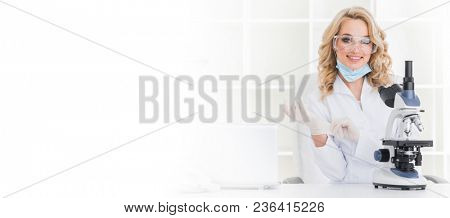 Beautiful female research scientist in lab coat and rubber gloves with microscope in laboratory