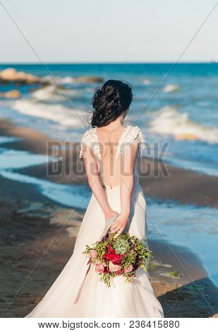 Beautiful Bride In Luxury Wedding Dress With Bouquet At The Sea Side. Wedding By The Sea. Bride Walk