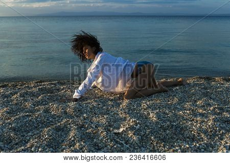 Woman Stands On All Fours, Creeps On Beach In Evening. Girl Sexy, Wears White Shirt And Bikini With