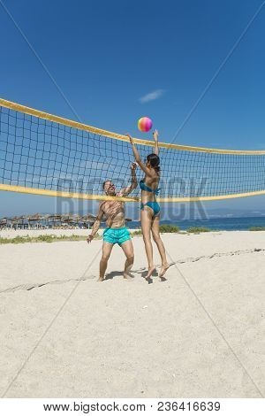 Young Sporty Active Couple Beat Off Volley Ball, Play Game On Summer Day. Woman And Man Fit, Strong,