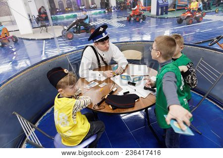 ST. PETERSBURG, RUSSIA - APRIL 5, 2018: Traffic officer issuing driver licenses for children in the traffic security place TachkiGrad. It's the Russia largest center for teaching the security on roads