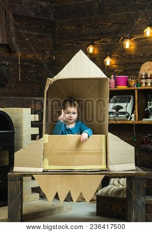 Kid Sit In Cardboard Hand Made Rocket, Pointing Upwards. Boy Play At Home With Rocket, Little Cosmon