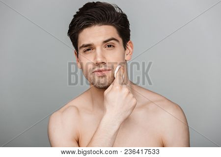 Beauty portrait of half naked handsome young man using cotton pad on his face isolated over gray background