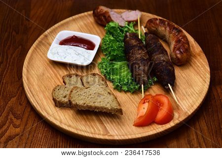 Meat Rolls On Wooden Skewers, Shish Kebab, Grilled Sausage Served With Tomato And Sour Cream Sauce O