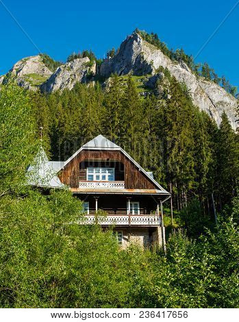 Wooden Cottage In The Valley. Stone Mountains. Carpathian Mountains In Romania. Beautiful House Or C