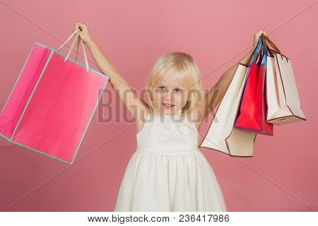 Small Girl Go Shopping. Child Smile With With Paper Bags In Shop. Kid Fashion And Beauty Look. Birth