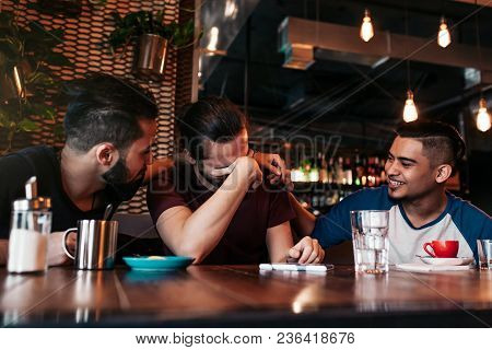 Happy Arabian Young Men Hanging In Loft Cafe. Group Of Mixed Race People Having Fun In Lounge Bar. F