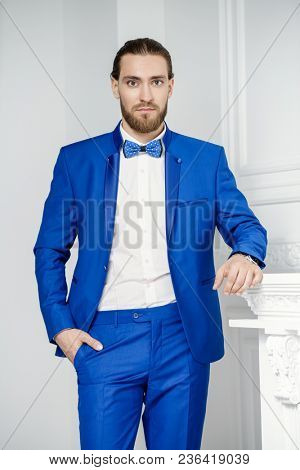Fashion shot. Handsome young man posing in elegant blue suit in luxurious apartments. Hair styling, barbershop. Men's beauty, fashion.