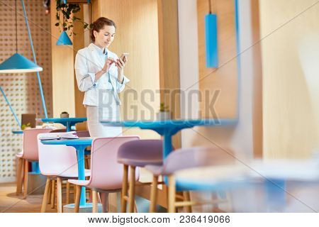Young female with smartphone messaging or reading notification while having break in cafe