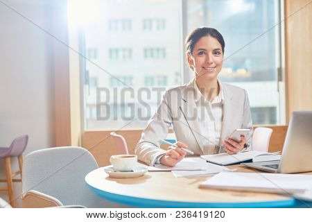 Young smiling businesswoman in formalwear working with papers by table and messaging in smartphone in cafe
