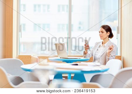 Contemporary mobile businesswoman reading message in her smartphone while sitting in front of laptop by table