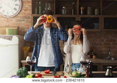 Happy Couple Cooking Healthy Food And Having Fun Together In Their Loft Kitchen At Home. Woman And M