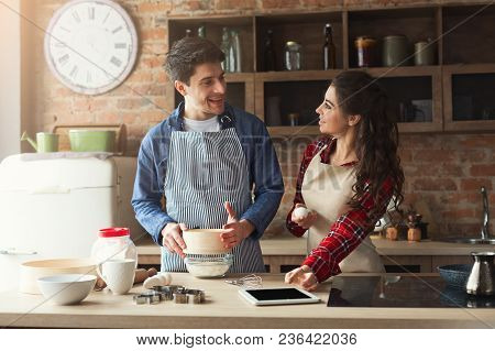 Happy Young Woman And Man Baking Pie In Loft Kitchen. Young Family Cooking At Home, Using Digital Ta