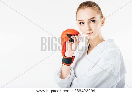 Female Karate Fighter Holding Mouthguard And Looking Away Isolated On White