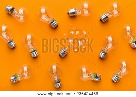 One Broken Light Bulb Among Whole Ones On Yellow Background, Top View. Creativity And Fragility Conc