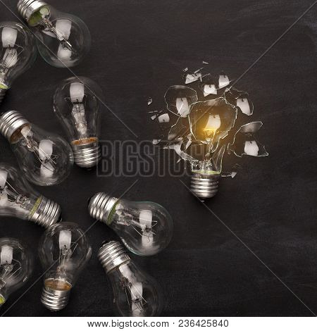 One Broken Glowing Light Bulb Against Whole Ones On Black Background, Top View. Creativity, Idea, Op