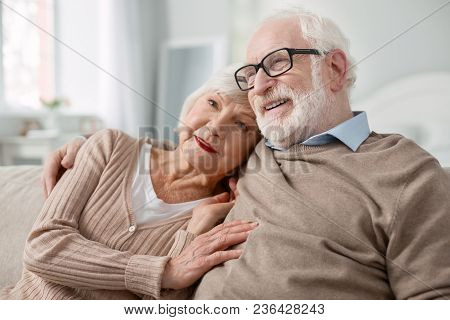 Family Relationships. Pleasant Nice Aged Woman Sitting Together With Her Husband While Hugging Him