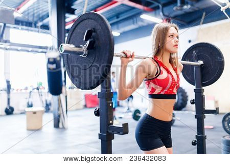 Portrait of young athletic woman squatting with barbell