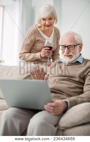 Distance Communication. Positive Nice Aged Couple Looking At The Laptop Screen While Making A Video