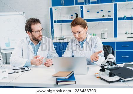 Portrait Of Scientists In Lab Coats And Eyeglasses Working Together At Workplace With Laptop In Lab