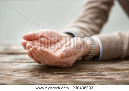 All Alone. Hand Of A Nice Sad Elderly Man Being Held Together While Being Put On The Table