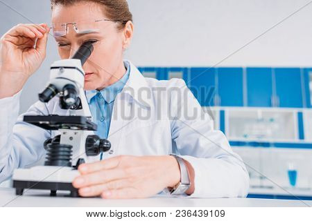 Female Scientist In Lab Coat And Eyeglasses Looking Through Microscope On Reagent In Lab