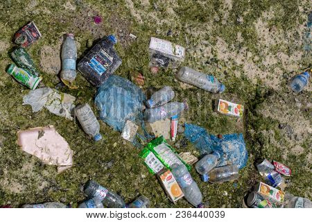 DOHA BAY, QATAR - April 16, 2018: Detritus left behind in Doha Bay, Qatar, by the outgoing tide - a mixture of plastic, metal and paper, and even a medicinal cream.