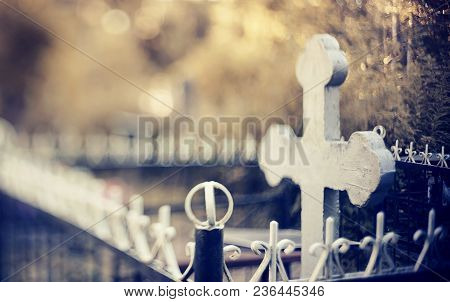 Blurry Background With A Cross On A Grave Behind A Fencing. It Is Photographed In The Free-lensing E