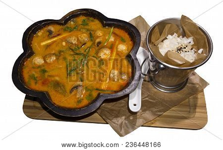 Hot Thai Soup Tom Yum (or Tom Yam) In A Curly Wooden Plate And A Bucket Of Rice Served On A Board Is