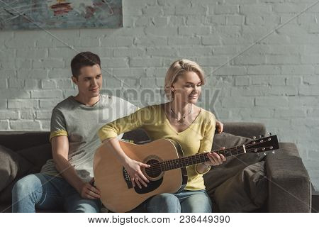 Girlfriend Playing Acoustic Guitar For Boyfriend At Home