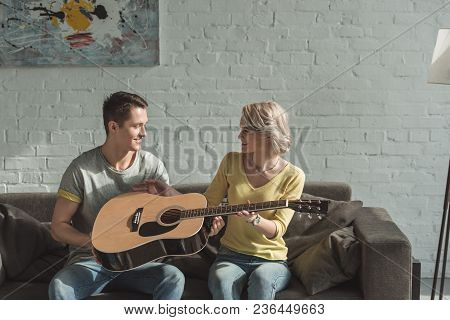 Boyfriend Giving Acoustic Guitar To Girlfriend At Home