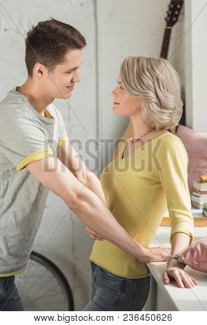 Affectionate Boyfriend And Girlfriend Looking At Each Other At Home