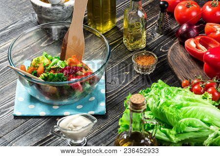 Man Preparing Salad With Fresh Vegetables On A Wooden Table. Cooking Tasty And Healthy Food. On Blac