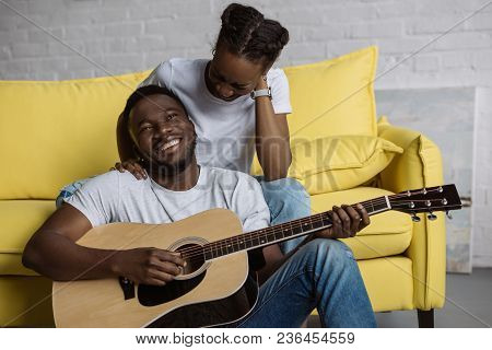 Young African American Woman Sitting On Sofa While Happy Boyfriend Playing Guitar