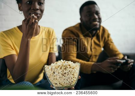 Cropped Shot Of African American Girl Eating Popcorn While Boyfriend Playing With Joystick At Home