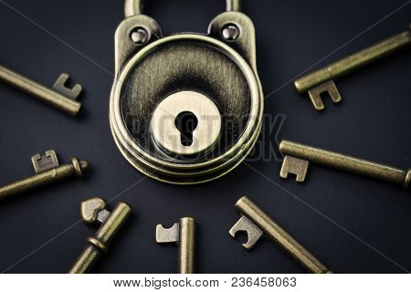 Security Or Secret Protection Concept, Vintage Brass Padlock Surrounded By Multiple Keys On A Dark B