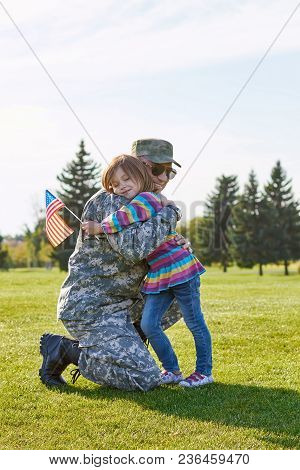Little Kid With Usa Flag Is Embracing Her Father. Military Daddy Is Hugging With His Little Daughter