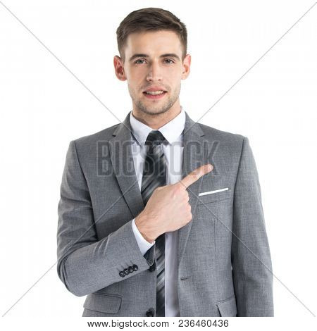 Portrait of young business man in suit pointing aside at copy space over white background