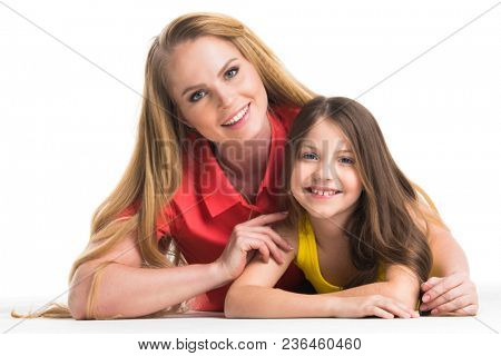 Mother and daughter lying on the floor, isolated on white background